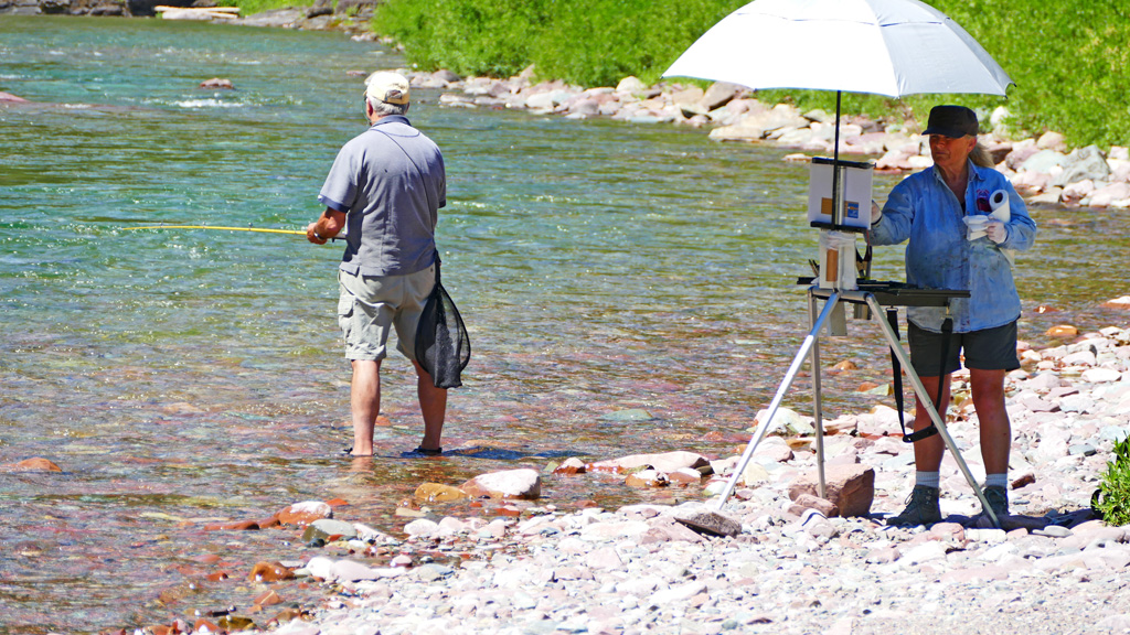 Photo of Gini painting and Randy fishing.
