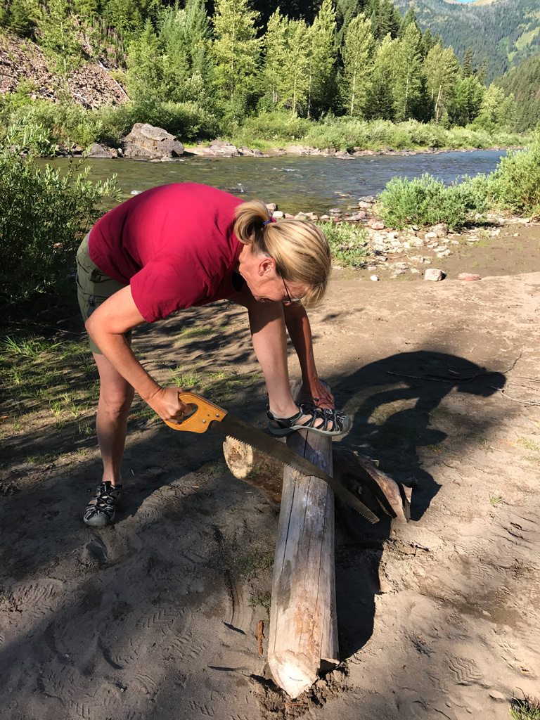 Photo of Francesca sawing a log.