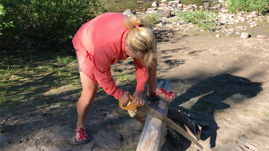 Photo of Gini Ogle sawing a log.