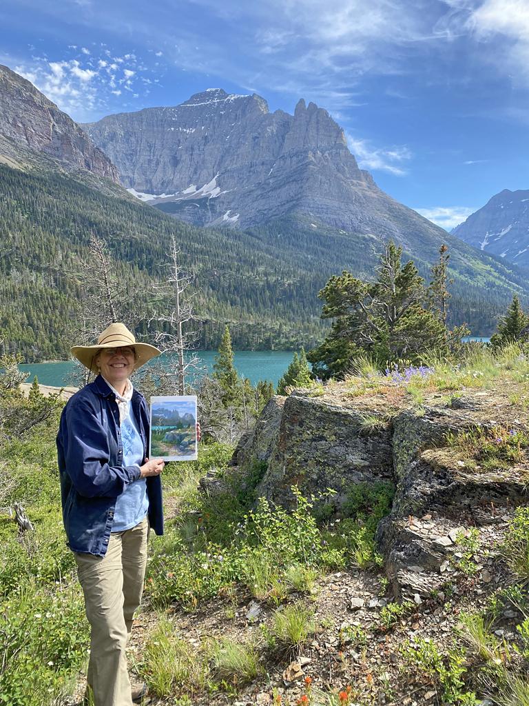 Photo of Francesca Droll holding plein air painting.